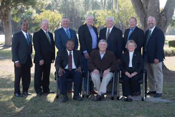 TCEC Board of trustees seated and standing outside of TCEC Headquarters in Madison